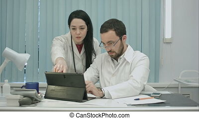Male and female doctors discuss results useing tablet
