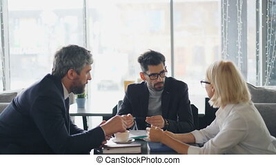 Male and female entrepreneurs discussing agreement during...