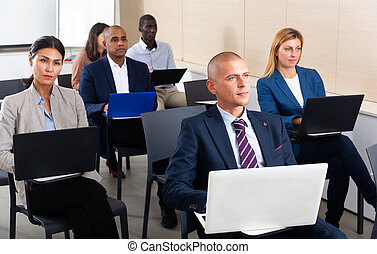 Male and female entrepreneurs with laptops participating in business training