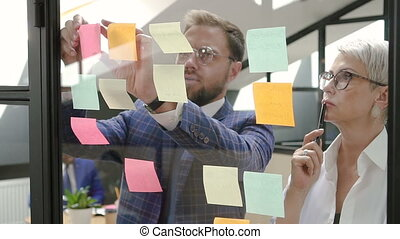 Male and female executive colleagues brainstorming project in office meeting room.