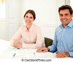 Male and female executive looking at you