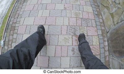 male feet in shoes go on paving stones - male and female...