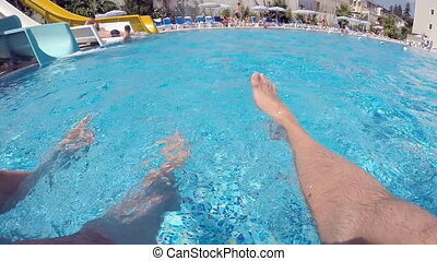 Male and female feet sprinkle water in pool. Young couple...