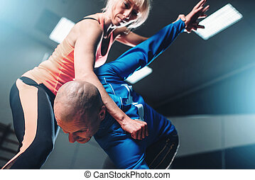 Male and female fighters, self-defense technique, self defense workout with personal instructor in gym, martial art