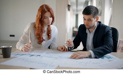 Male and female financial consultants discussing current...