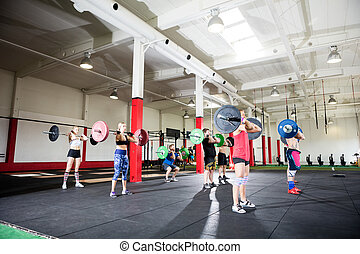 Male And Female Friends Lifting Barbells