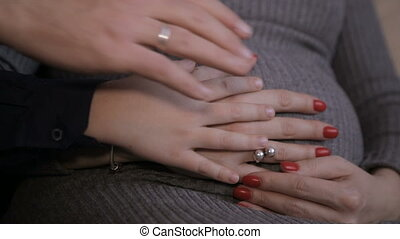 Male and female hands caress pregnant belly - Male and...
