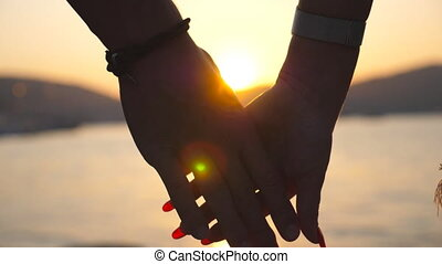 Male and female hands comforting and stroking each other at sunset against an sea background. Young couple joining arms outdoor. Summer vacation. Concept of loving and happiness. Close up Slow motion