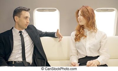 Male and female lawers talking in private jet. Man in suit...
