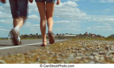 Male and female legs walking on summer countryside highway - traveling concept