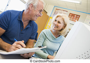 Male and female mature students working together on a computer