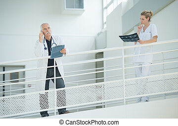 male and female physicians talking on the balcony
