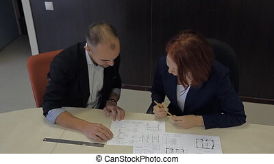 male and female professionals working together on a blueprint house schemes.