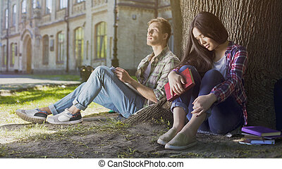 Male and female strangers sitting under tree, first meeting, indecisiveness