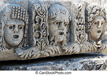 Male and female theatrical mask carved on stone surface