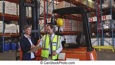 Male and female warehouse managers talking in a warehouse ...