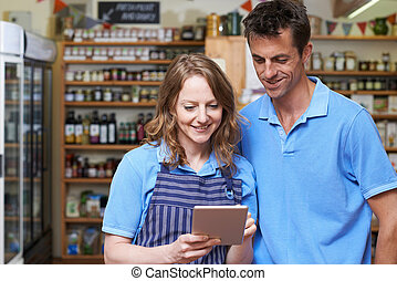 Male And Female Workers In Delicatessen Store Using Digital Tablet