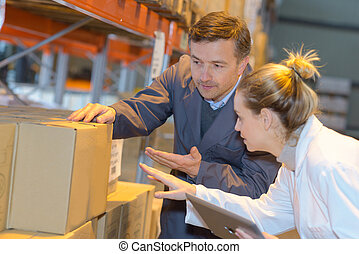 male and female workers looking at box in warehouse