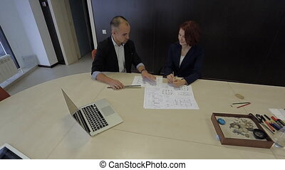 male and female working together on a blueprint house schemes. professionals