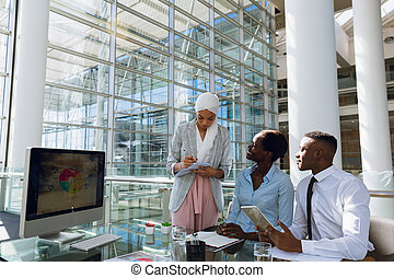 Male and females executives working together at desk in ...