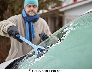 The mid adult man cleans a frozen windshield - focus on ice scraper, horizon format