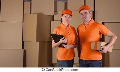 Male anf female couriers in orange uniform standing against brown cardboard boxes backround. Delivery company staff, 4K shot