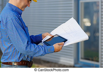 Midsection of male architect holding digital tablet and blueprint