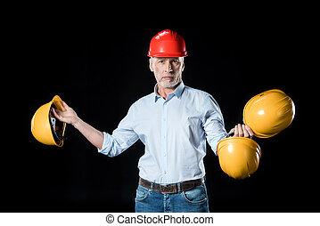 male architect in helmet holding blueprint on black