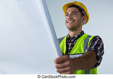 Male architect looking at blueprint against white background