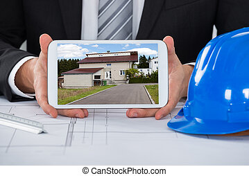Male Architect Showing Picture Of House On Digital Tablet