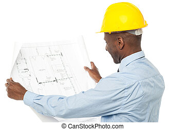 Male architect viewing blue print