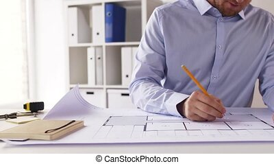 male architect with blueprint taking notes