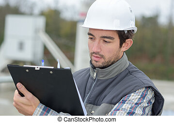 male architect with blueprints reading clipboard outdoors