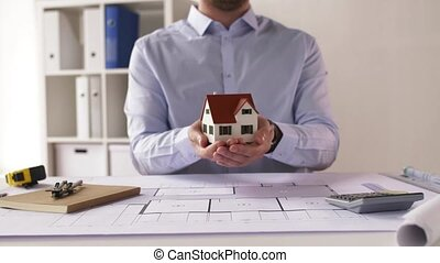 male architect with house model and blueprint -...