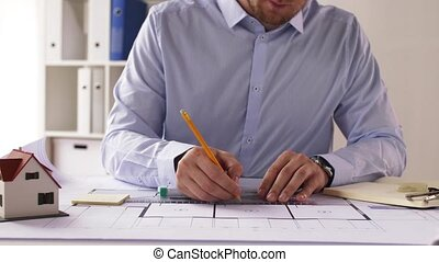 male architect with ruler measuring blueprint