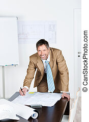 Male Architect Working On Blue Print At Desk In Office
