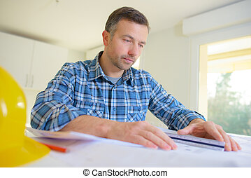 male architect working on blueprints