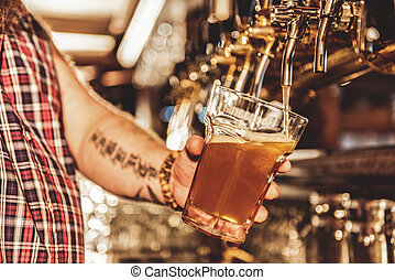 Male arm filling cup of beer