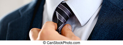 Male arm in blue suit set tie closeup. White collar...