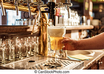 Male arm keeping pouring beer in alehouse