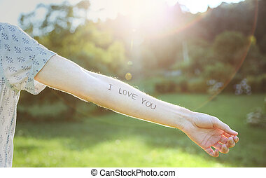 Male arm with text -I love you- written in skin