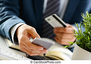 Male arms in suit hold credit card and phone