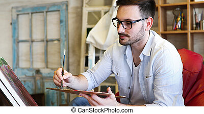 Male art school artist painting with oil on canvas