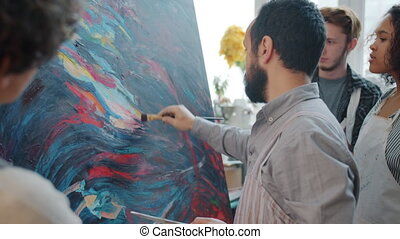 Male artist creating beautiful abstract picture while people...