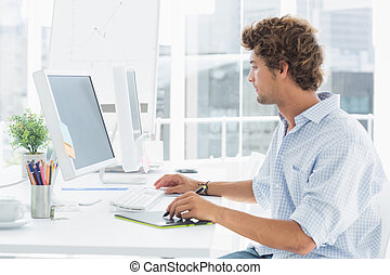 Male artist drawing something on graphic tablet with pen