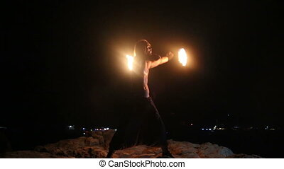 Male Artist of the spins fire poi on a rock at night on a background of town