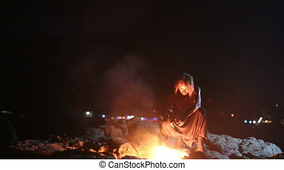 Male Artist of the spins fire poi on a rock at night on a...