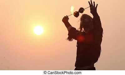 Male Artist of the spins fire poi on a rock at sunset on a background of the sea waves and birds