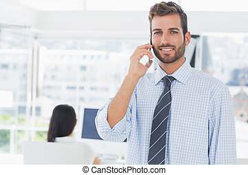 Male artist using mobile phone with colleague in background