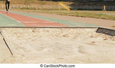 Male athlet makes a long jump at the stadium